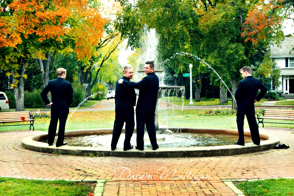 groomsmen pretend to pee into fountain in their wedding photos
