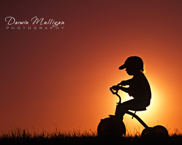 Child on a trike, silhouette, sunset in background