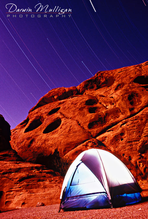 Lightpainted tent and rock formation with star trails nightime timelapse photograph Valley of Fire State Park Nevada