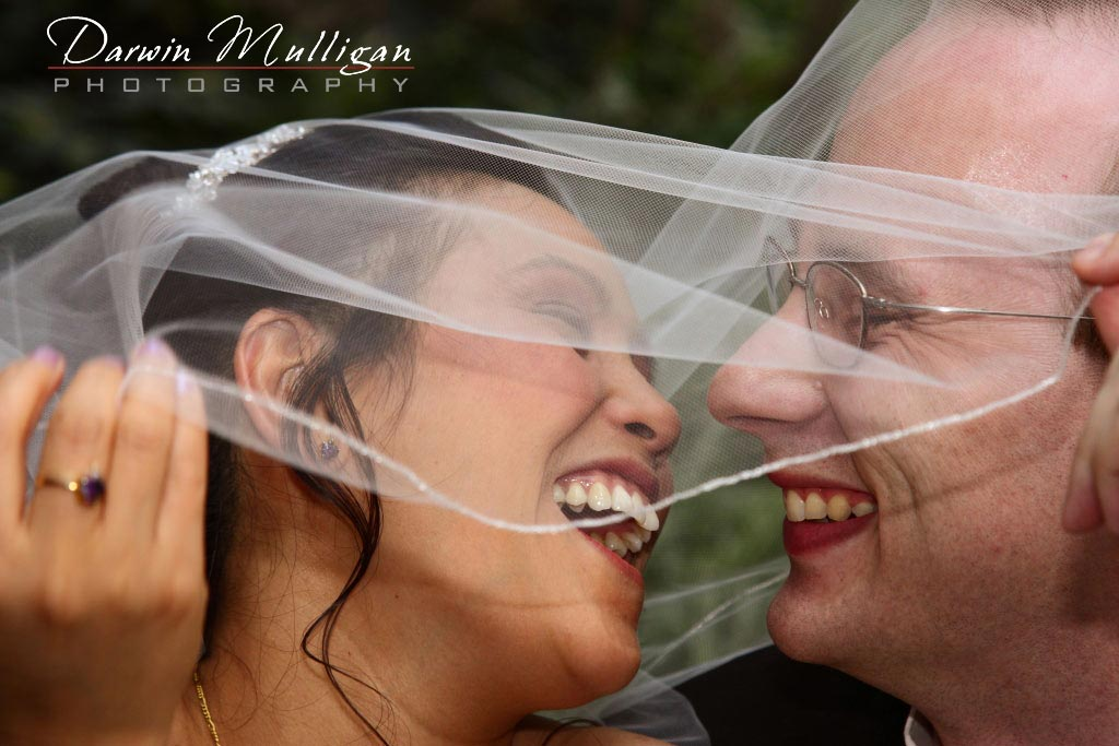 Sheryl and Anthony hide behind her veil to kiss