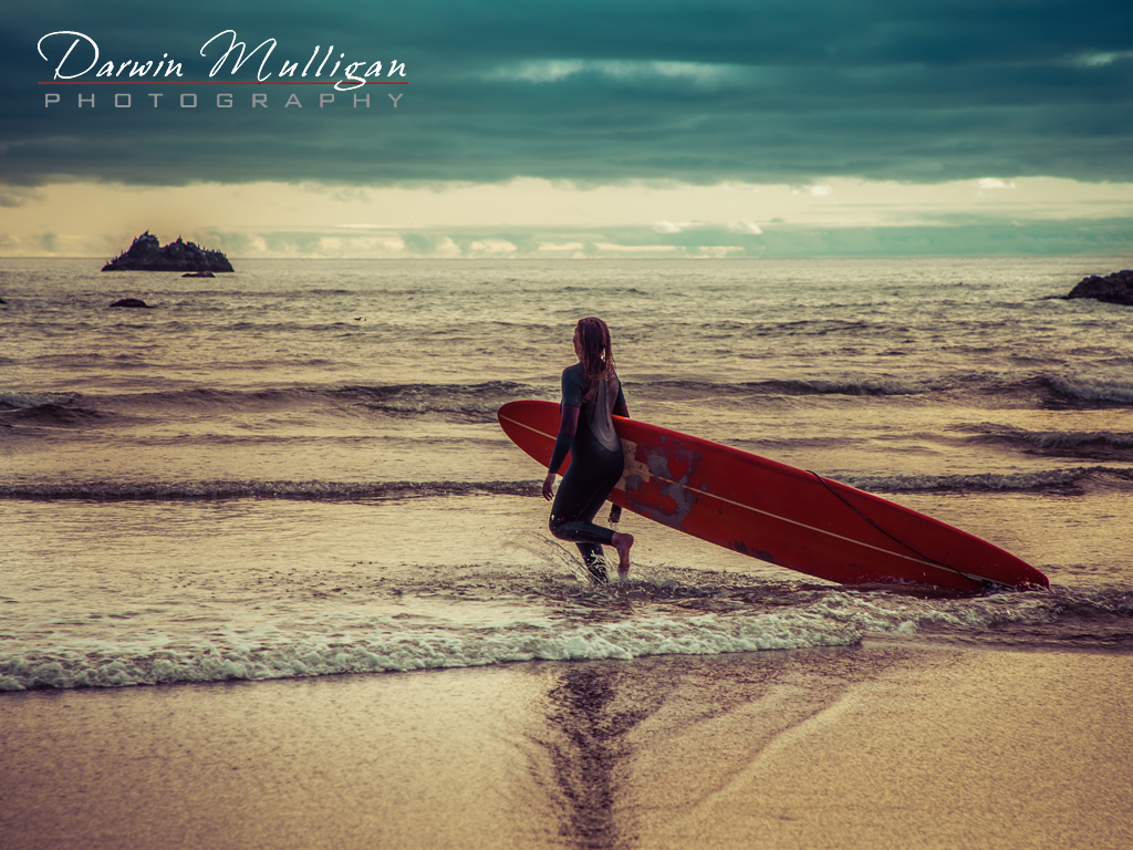 Surfer girl at sunset at Cannon Beach on the Oregon Coast